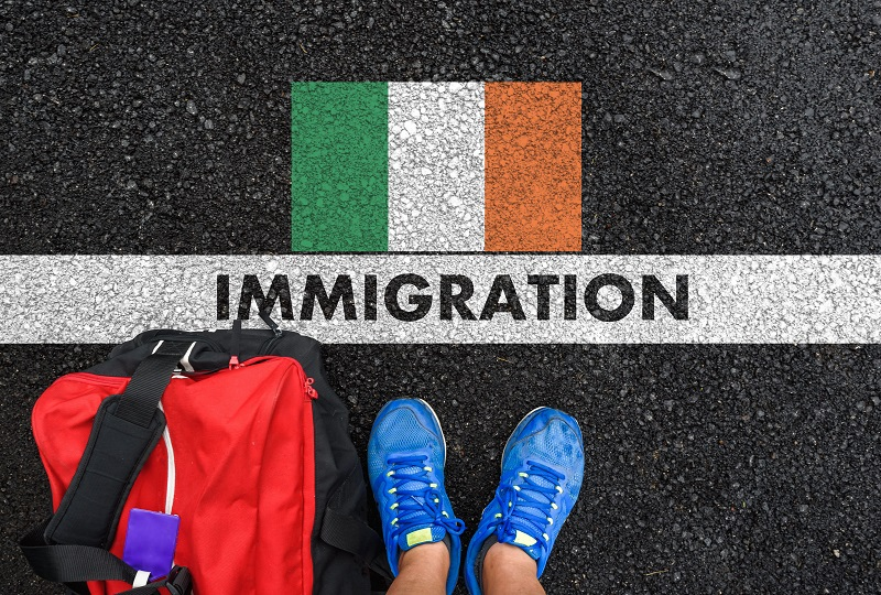 Man in shoes with bag standing next to line with word IMMIGRATION and flag of Ireland on asphalt road
